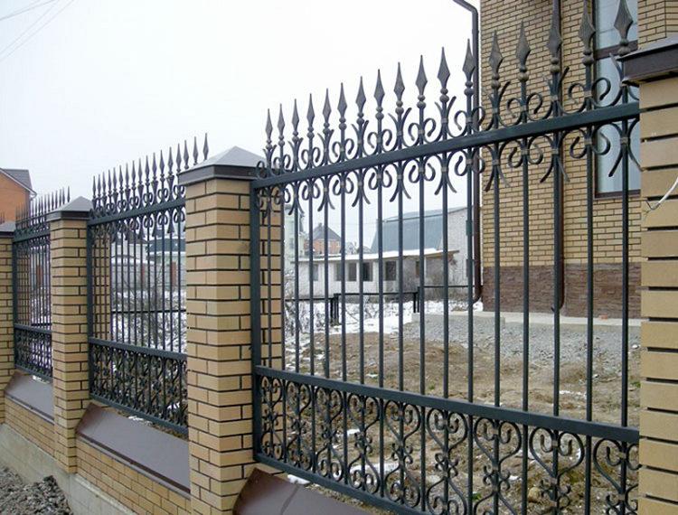 забор из кованного металла с кирпичными столбами